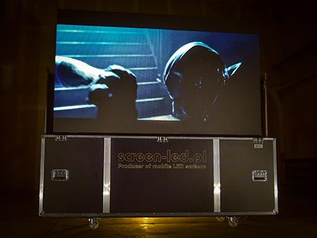 TVcase in dark room with Sci-fi movie on the screen.